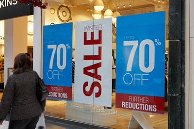 LEEDS, WEST YORKSHIRE, UK: JANUARY 4, 2009: People walking past shop window price reduction sale signs